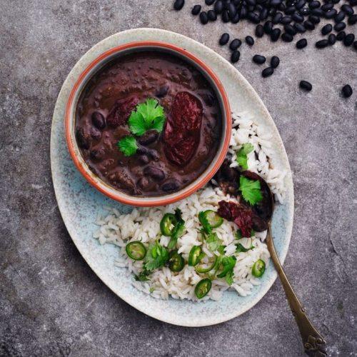 Over hele Latin- og Sydamerika findes utallige variationer over samme tema: bønner og ris. Det er billige retter, og de er smækfulde af smag. Denne version bruger den røgede og spicy chipotle-chili, som fås på dåser hos velassorterede grønthandlere. Brug alternativt frisk chili eller stødt og røget chilipulver - det giver også en dyb fin chilismag. Opskrift Erin Chapman og Grace Løvig og foto Kam.
